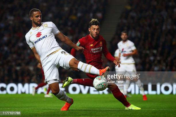 Jordan Bowery of MK Dons battles for possession with Alex OxladeChamberlain of Liverpool during the Carabao Cup Third Round match between Milton...