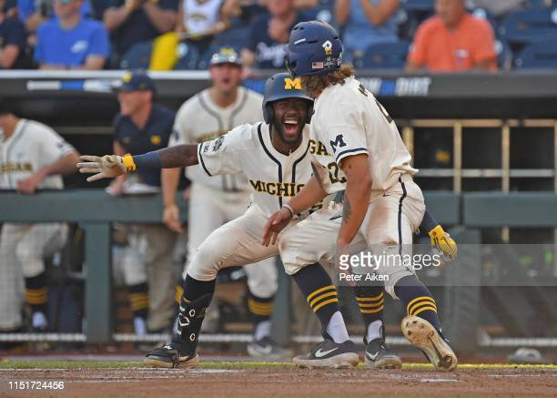 Jordan Brewer of the Michigan Wolverines celebrates with teammate Christan Bullock after scoring a run in the first inning against the Vanderbilt...