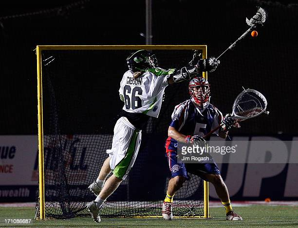 Jordan Burke of the Boston Cannons defends the net as Matt Gibson of the New York Lizards shoots on net in the second half at Harvard Stadium on June...
