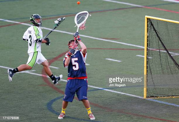 Jordan Burke of the Boston Cannons makes a save as Rob Pannell of the New York Lizards watches in the first half at Harvard Stadium on June 21 2013...