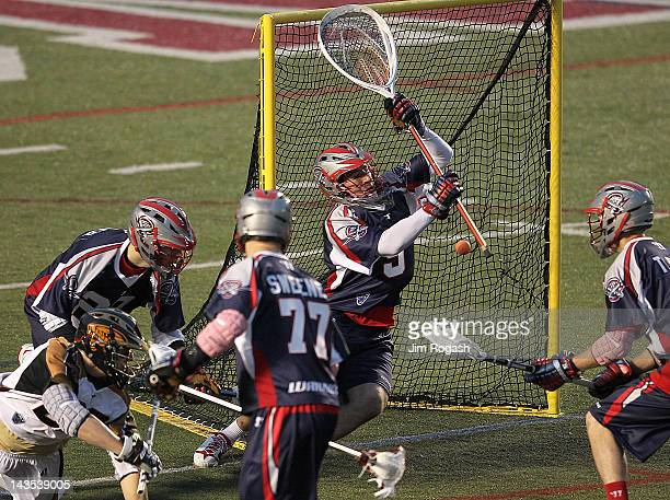 Jordan Burke of the Boston Cannons makes a save on a shot by Sean Delaney of the Rochester Rattlers at Harvard Stadium April 28 2012 in Boston...