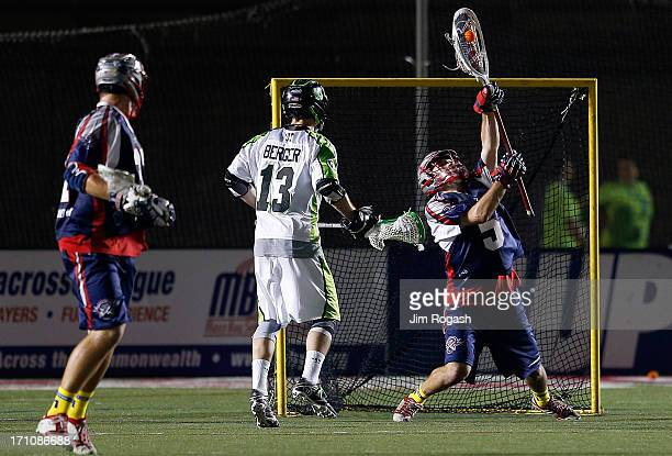 Jordan Burke of the Boston Cannons makes a save under pressure from Stephen Berger of the New York Lizards in the second half at Harvard Stadium on...
