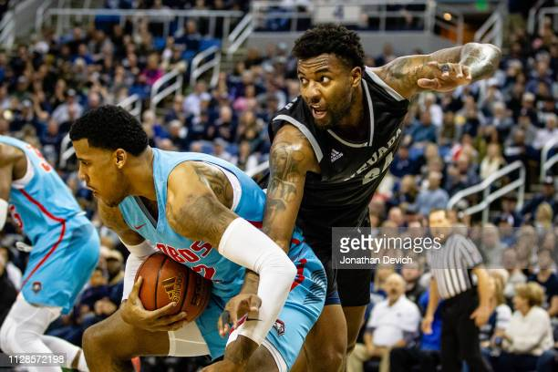Jordan Caroline of the Nevada Wolf Pack tangles with Vance Jackson of the New Mexico Lobos as they go after a rebound at Lawlor Events Center on...