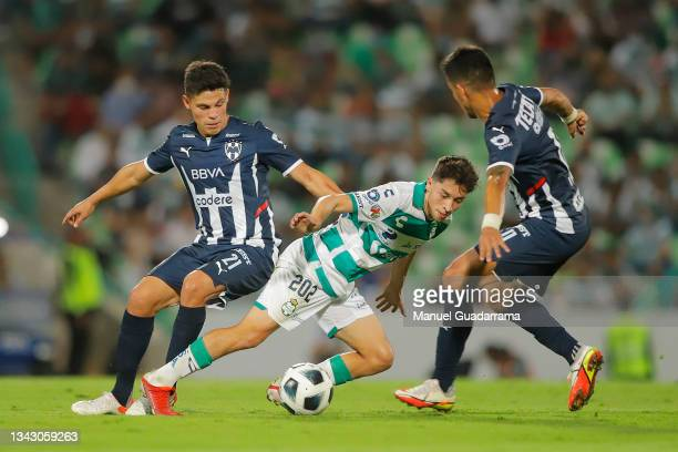 Jordan Carrillo of Santos struggles for the ball with Maximiliano Meza and Arturo Gonzalez of Monterrey during the 10th round match between Santos...