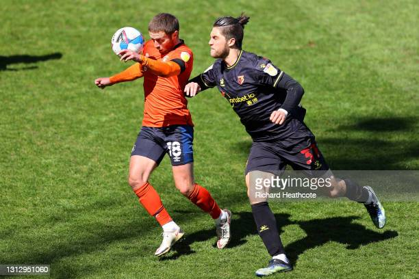 Jordan Clark of Luton Town battles for possession with Francisco Sierralta of Watford FC during the Sky Bet Championship match between Luton Town and...