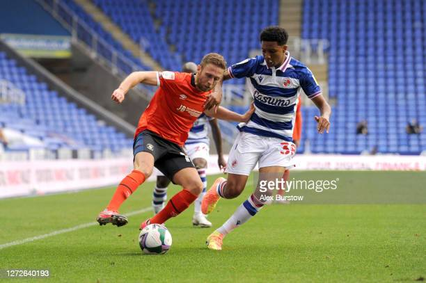 Jordan Clark of Luton Town is challenged by Ethan Bristow of Reading FC during Carabao Cup Second Round match between Reading FC and Luton Town at...