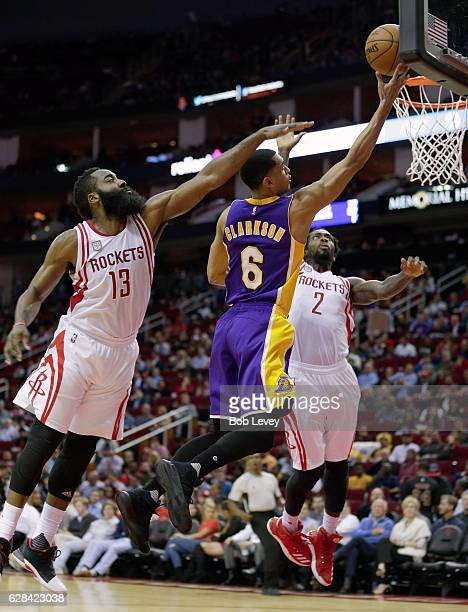 Jordan Clarkson of the Los Angeles Lakers drives to the basket between James Harden of the Houston Rockets and Patrick Beverley at Toyota Center on...
