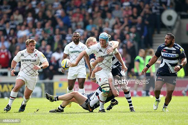Jordan Crane of Leicester Tigers offloads in the tackle by Marc Jones and David Seymour of Sale Sharks to team mate Tom Youngs during the Aviva...