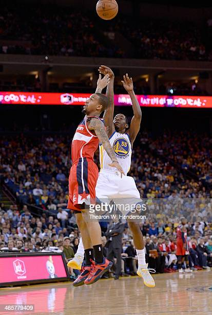 Jordan Crawford of the Golden State Warriors shoots over Eric Maynor of the Washington Wizards at ORACLE Arena on January 28 2014 in Oakland...