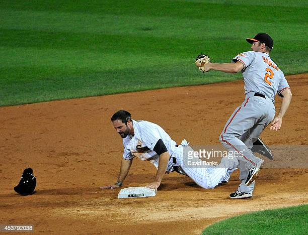 Jordan Danks of the Chicago White Sox is tagged out at second base by JJ Hardy of the Baltimore Orioles during the third inning on August 18 2014 at...
