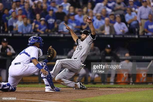 Jordan Danks of the Chicago White Sox runs home to score against Salvador Perez of the Kansas City Royals at Kauffman Stadium on September 17 2014 in...