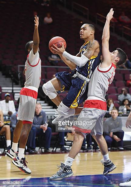 Jordan Davis of the Northern Colorado Bears drives to the basket between Quincy McKnight and Sean Hoehn of the Sacred Heart Pioneers during the 2016...
