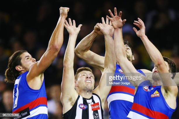 Jordan de Goey of the Magpies is crunched by Tom Boyd of the Bulldogs Easton Wood and Bailey Williams of the Bulldogs during the round 10 AFL match...