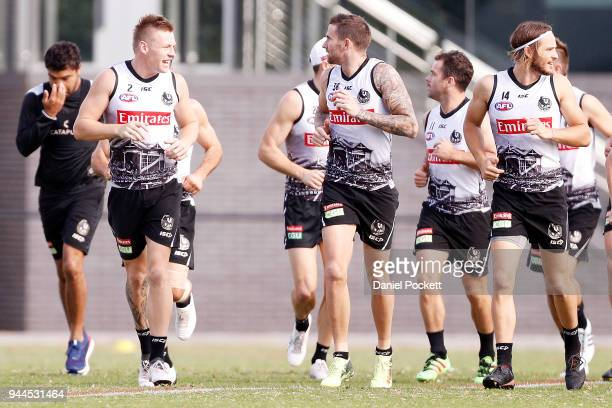 Jordan De Goey of the Magpies Jeremy Howe of the Magpies and James Aish of the Magpies warm up with the team during a Collingwood Magpies AFL...