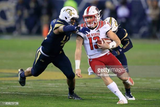Jordan Domineck of the Georgia Tech Yellow Jackets reaches for Devin Leary of the North Carolina State Wolfpack during the college football game...