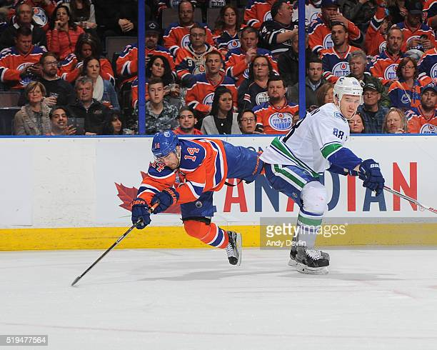 Jordan Eberle of the Edmonton Oilers battles for the puck against Nikita Tryamkin of the Vancouver Canucks on April 6 2016 at Rexall Place in...
