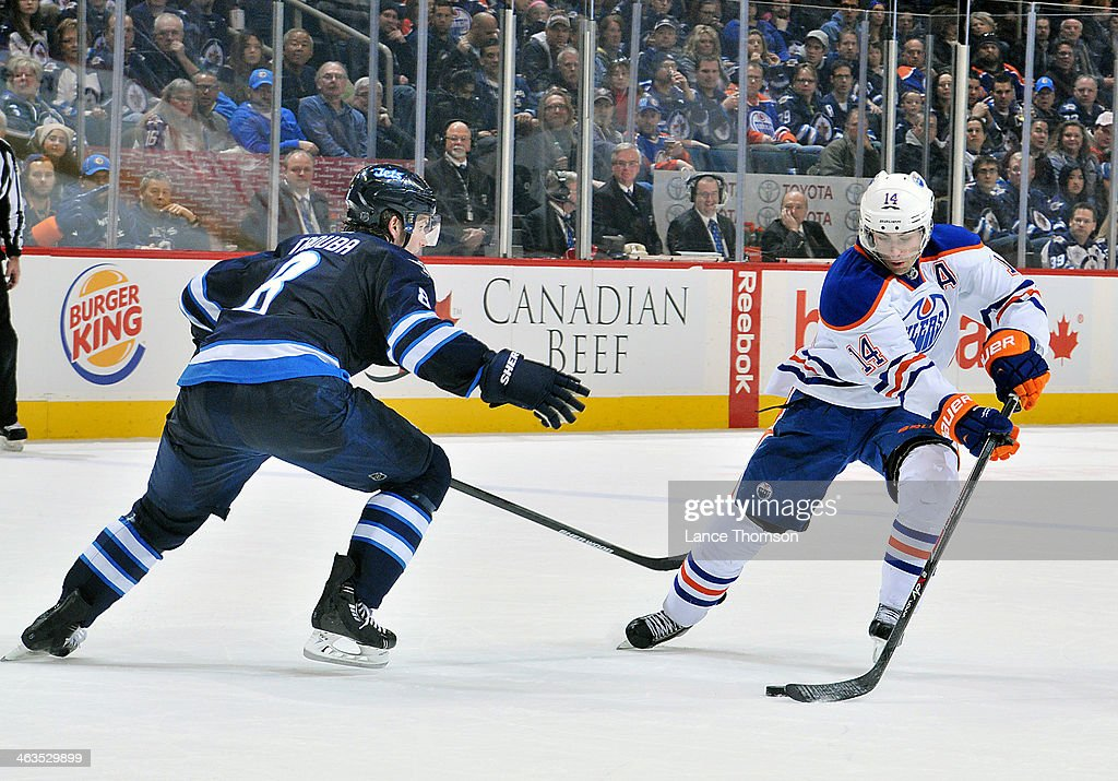 Jordan Eberle #14 of the Edmonton Oilers carries the puck up the ice as Jacob Trouba #8 of the Winnipeg Jets defends during third period action at the MTS Centre on January 18, 2014 in Winnipeg, Manitoba, Canada.