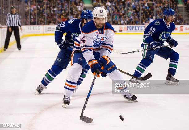 Jordan Eberle of the Edmonton Oilers corrals the loose puck after getting past Ben Hutton and Jayson Megna of the Vancouver Canucks in NHL action on...