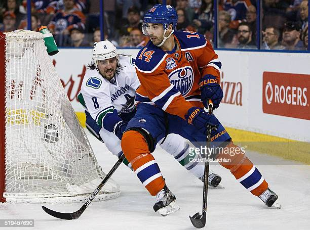 Jordan Eberle of the Edmonton Oilers is pursued by Christopher Tanev of the Vancouver Canucks on April 6 2016 at Rexall Place in Edmonton Alberta...