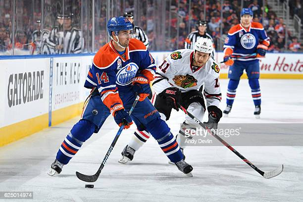 Jordan Eberle of the Edmonton Oilers skates with the puck while being pursued by Andrew Desjardins of the Chicago Blackhawks on November 21 2016 at...