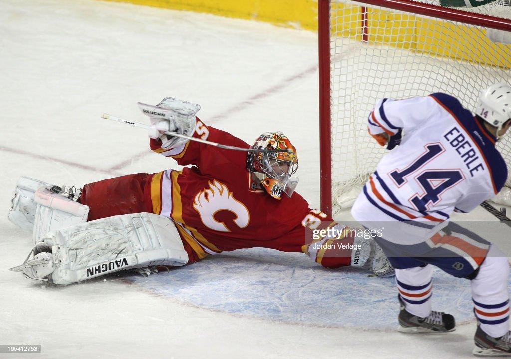 Jordan Eberle #14 of the Edmonton Oilers slips the puck past goalie Joey MacDonald #35 of the Calgary Flames at Scotiabank Saddledome on April 3, 2013 in Calgary, Alberta, Canada.