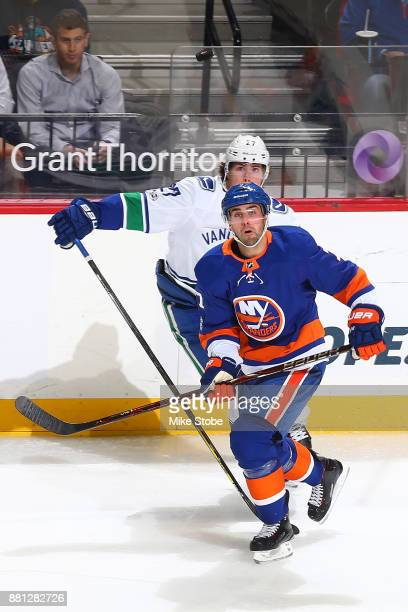 Jordan Eberle of the New York Islanders and Ben Hutton of the Vancouver Canucks keep their eye on the loose puck at Barclays Center on November 28...