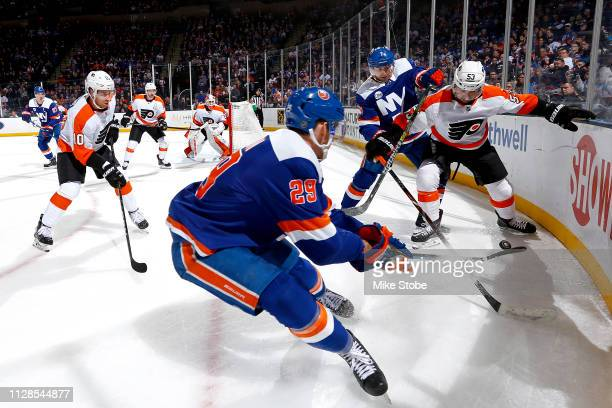 Jordan Eberle of the New York Islanders and Shayne Gostisbehere of the Philadelphia Flyers battle for the puck during the first period at NYCB Live's...