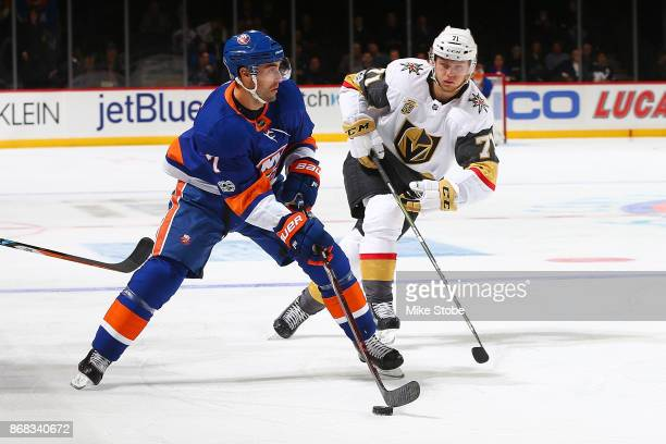 Jordan Eberle of the New York Islanders carries the puck in the offensive zone amid pressure from William Karlsson of the Vegas Golden Knights at...