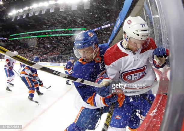 Jordan Eberle of the New York Islanders checks Brett Kulak of the Montreal Canadiens into the boards during the second period at the Barclays Center...