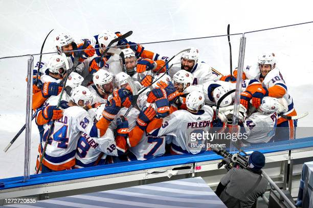 Jordan Eberle of the New York Islanders is congratulated by his teammates after scoring the game-winning goal against the Tampa Bay Lightning during...