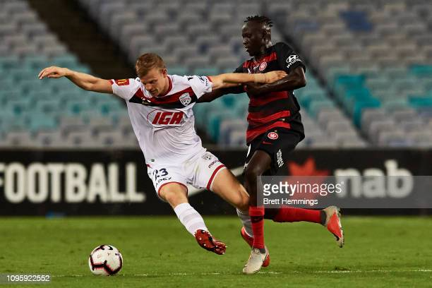 Jordan Elsey of Adelaide is tackled during the round 14 ALeague match between the Western Sydney Wanderers and Adelaide United at ANZ Stadium on...