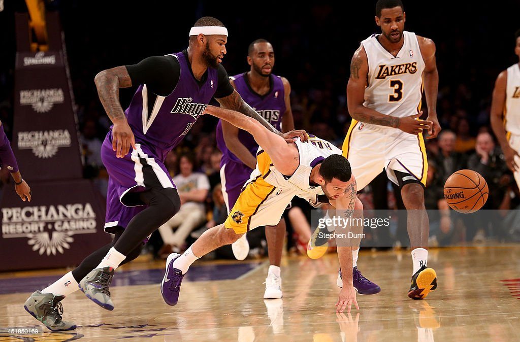 Jordan Farmar #1 of the Los Angeles Lakers and DeMarcus Cousins #15 of the Sacramento Kings go for a loose ball at Staples Center on November 24, 2013 in Los Angeles, California. The Lakers won 100-86.