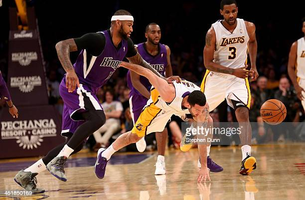 Jordan Farmar of the Los Angeles Lakers and DeMarcus Cousins of the Sacramento Kings go for a loose ball at Staples Center on November 24 2013 in Los...