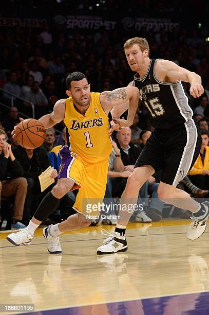 Jordan Farmar of the Los Angeles Lakers drives to the basket against Matt Bonner of the San Antonio Spurs on November 1 2013 at STAPLES Center in Los...