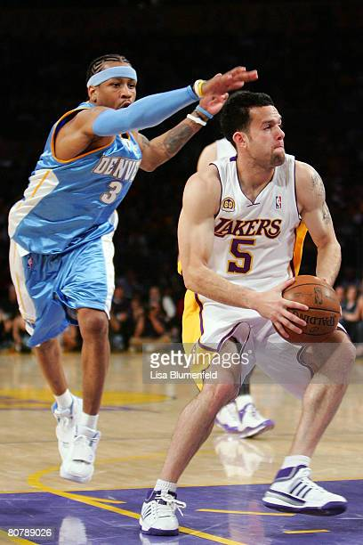 Jordan Farmar of the Los Angeles Lakers moves the ball as Allen Iverson of the Denver Nuggets looks to steal it from behind in the second quarter of...