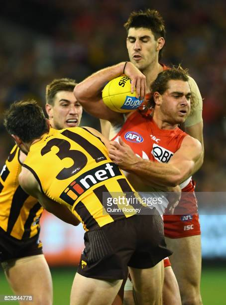 Jordan Foote of the Swans is tackled by Ricky Henderson of the Hawks during the round 19 AFL match between the Hawthorn Hawks and the Sydney Swans at...