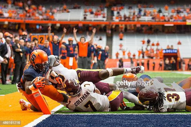 Jordan Fredericks of the Syracuse Orange dives in for a touchdown in overtime to win the game against the Central Michigan Chippewas on September 19...