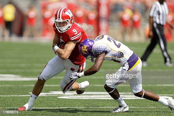 Jordan Fredrick of the Wisconsin Badgers makes the catch and turns upfield before getting tackled by James Huguely of the Tennessee Tech Golden...