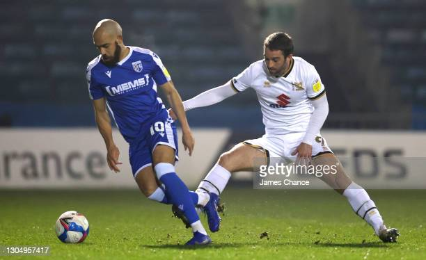 Jordan Graham of Gillingham FC is challenged by Will Grigg of Milton Keynes Dons during the Sky Bet League One match between Gillingham and Milton...