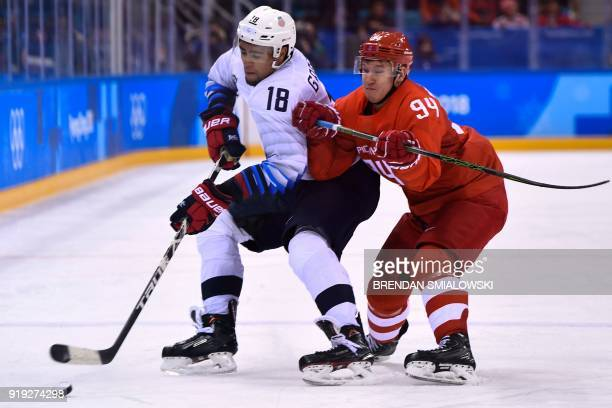 Jordan Greenway and Russia's Alexander Barabanov vie for the puck in the men's ice hockey preliminary round group B game between the Olympic Athletes...