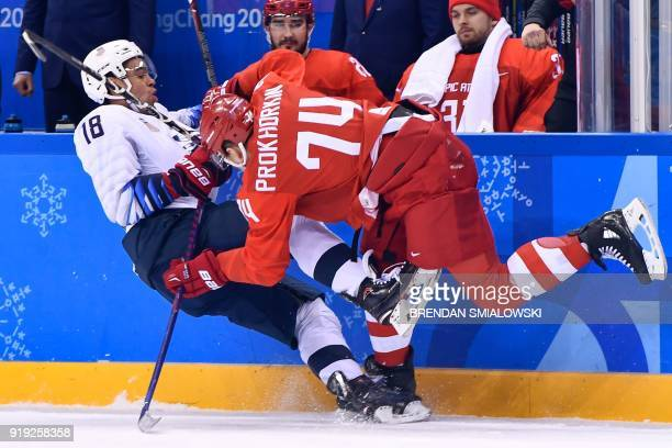 Jordan Greenway and Russia's Nikolai Prokhorkin in action during the men's ice hockey preliminary round group B game between the Olympic Athletes...
