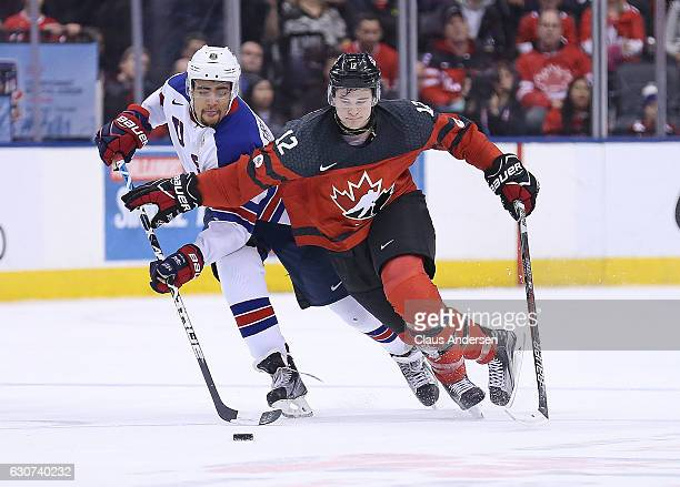 Jordan Greenway of Team USA looks to steal a puck from Julien Gauthier of Team Canada during a preliminary round game in the 2017 IIHF World Junior...