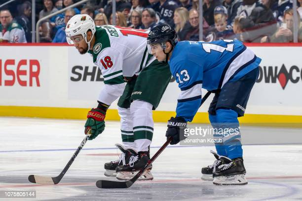 Jordan Greenway of the Minnesota Wild and Brandon Tanev of the Winnipeg Jets gets set during a first period face-off at the Bell MTS Place on...