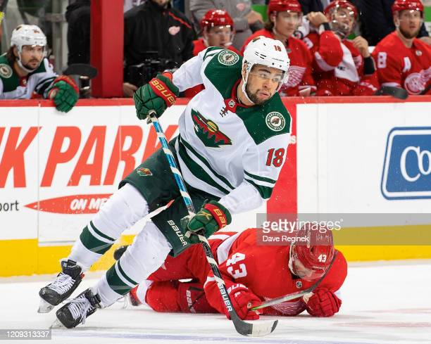 Jordan Greenway of the Minnesota Wild avoids a check from Darren Helm of the Detroit Red Wings during an NHL game at Little Caesars Arena on February...