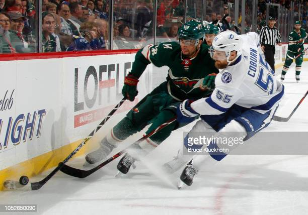 Jordan Greenway of the Minnesota Wild skates with the puck as Braydon Coburn of the Tampa Bay Lightning defends during a game between the Minnesota...