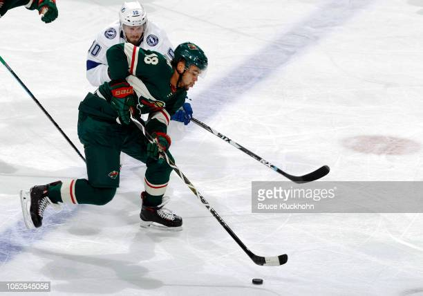 Jordan Greenway of the Minnesota Wild skates with the puck as J.T. Miller of the Tampa Bay Lightning defends during a game between the Minnesota Wild...