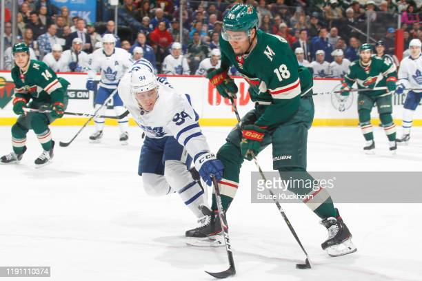 Jordan Greenway of the Minnesota Wild skates with the puck while Tyson Barrie of the Toronto Maple Leafs defends during the game at the Xcel Energy...