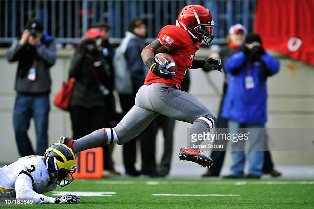 Jordan Hall of the Ohio State Buckeyes eludes the tackle attempt of Marvin Robinson of the Michigan Wolverines on his way to an 85yard kick return...
