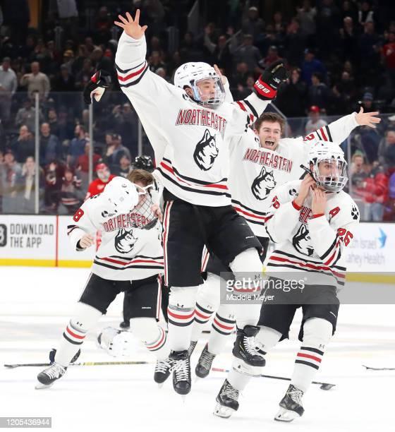 Jordan Harris of the Northeastern Huskies, center, celebrates with teammates after scoring the game winning goal to defeat the Boston University...