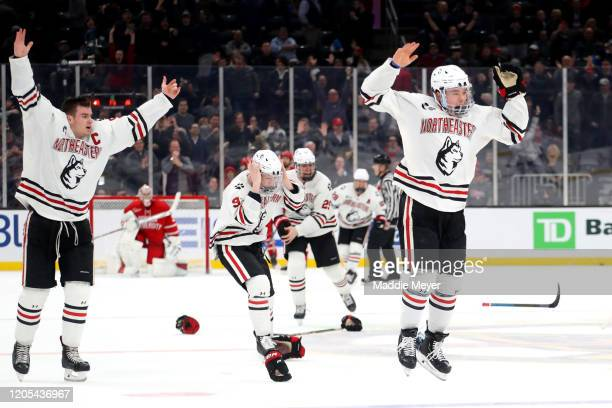 Jordan Harris of the Northeastern Huskies, right, celebrates with teammates after scoring the game winning goal to defeat the Boston University...